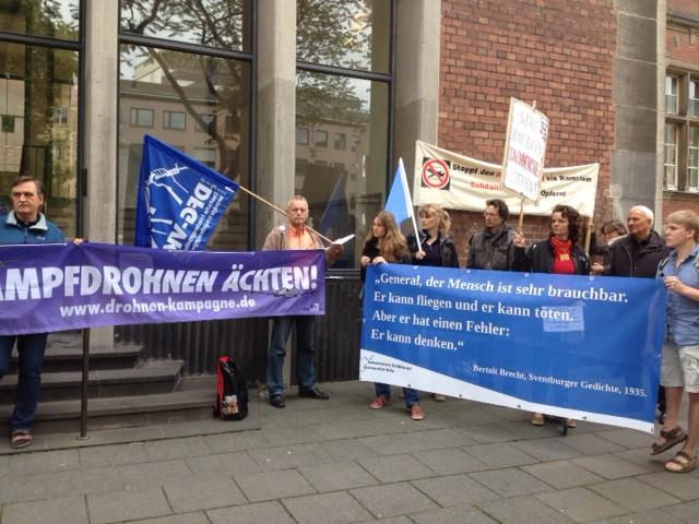 Mehrere Personen zeigen Banner, Transparente und Fahnen gegen den Drohnenkrieg.