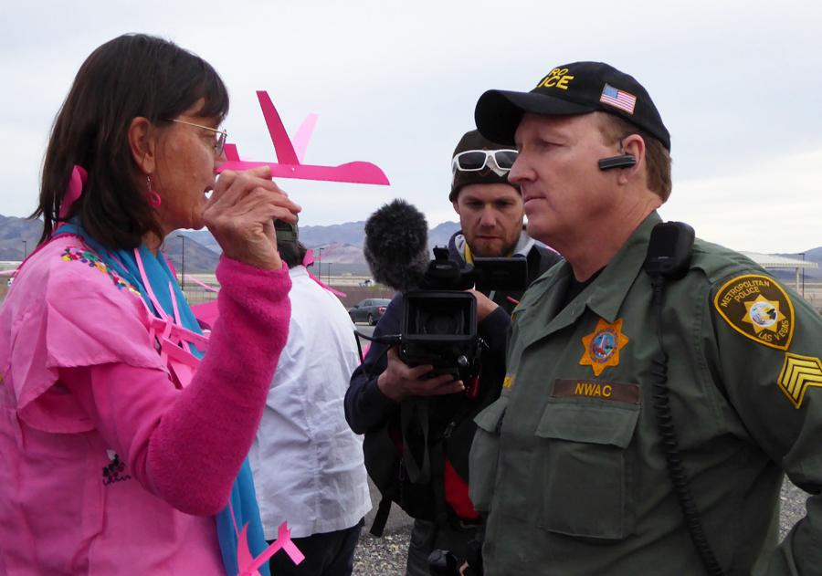 Links ist eine Frau mit glatten dunklen Haaren zu sehen, die ein pinkfarbenes T-Shirt trägt und eine pinkfarbene Papierdrohne in der rechten Hand hält. Sie spricht mit einem Polizisten in olivfarbener Uniform und Baseballkappe, der ihr mit unbewegter Mine zuhört.