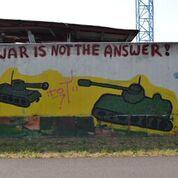 Das Graffito zeigt zwei olivgrüne Panzer, die sich schussbereit gegenüberstehen auf gelbem Hintergrund. Dazwischen steht ein rotes Strichmännchen, das sie auseinanderhält.