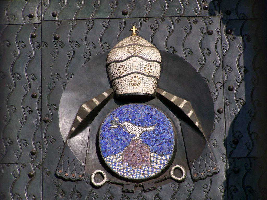 Das Bild zeigt eine künstlerische Verzierung einer Bronzetür des Kölner Doms: die Friedenstaube mit einem Ölbaumzweig im Schnabel vor himmelblauem Hintergrund; darüber die Bischofsmütze mit der Stola.