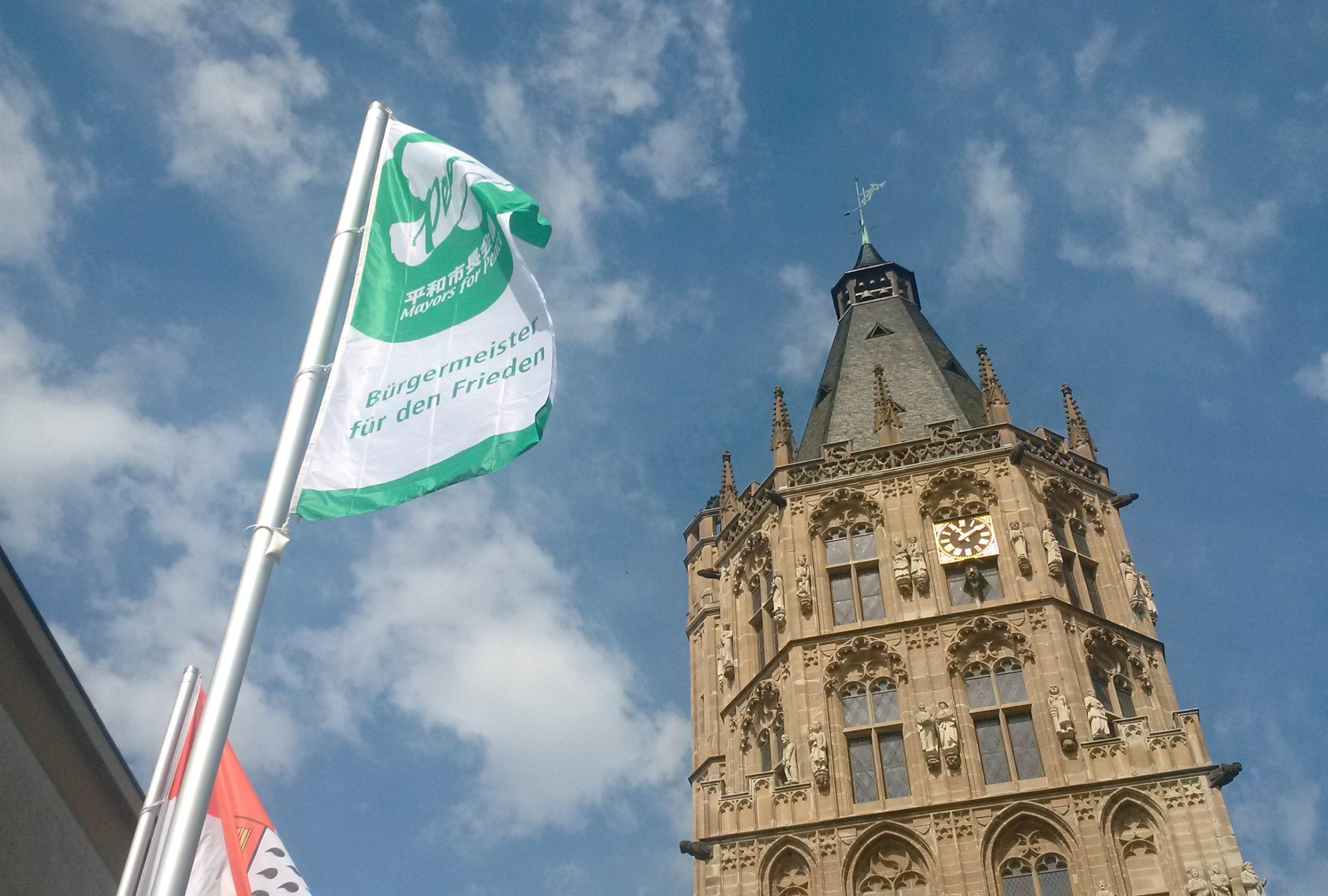 Die Mayors-for-Peace-Flagge trägt eine grüne Aufschrift auf weißem Grund. Hier flattert sich vor dem Kölner Rathausturm. Das Foto ist von unten aufgenommen, sodass man den blauen Himmel und weiße Wölkchen im Hintergrund sieht.