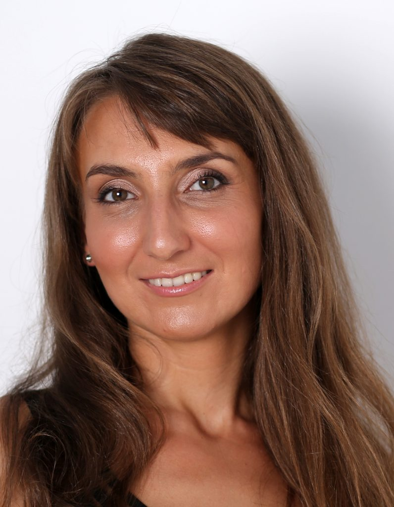 Porträtfoto: eine freundlich blickende junge Frau mit langen braunen Haaren