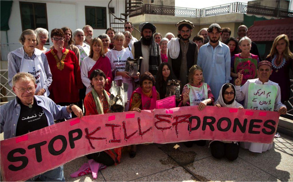 """Eine große Gruppe von europäisch und pakistanisch-indisch aussehenden Menschen jeden Alters versammeln sich hinter einem selbst beschrifteten pinkfarbenen Transparent mit der Aufschrift """"Stop Killer Drones!"""""""