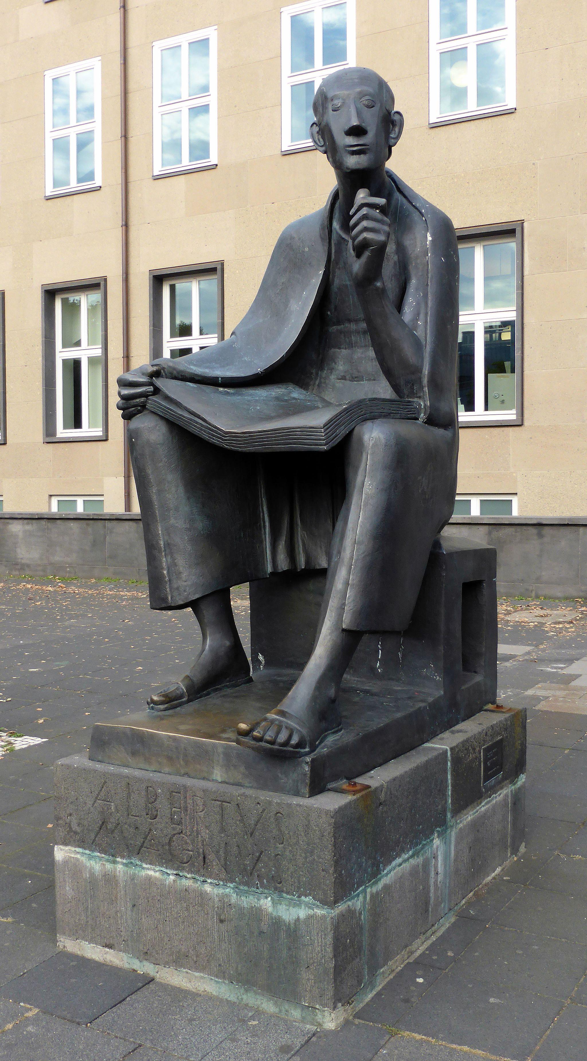 Das Albertus-Magnus-Denkmal ist wahrscheinlich aus Bronze. Es zeigt einen lesenden, barfüßigen Mann mit Umhang. Im Hintergrund das Hauptgebäude der Kölner Universität mit hohen Fenstern, in denen weiße Fensterkreuze zu sehen sind.