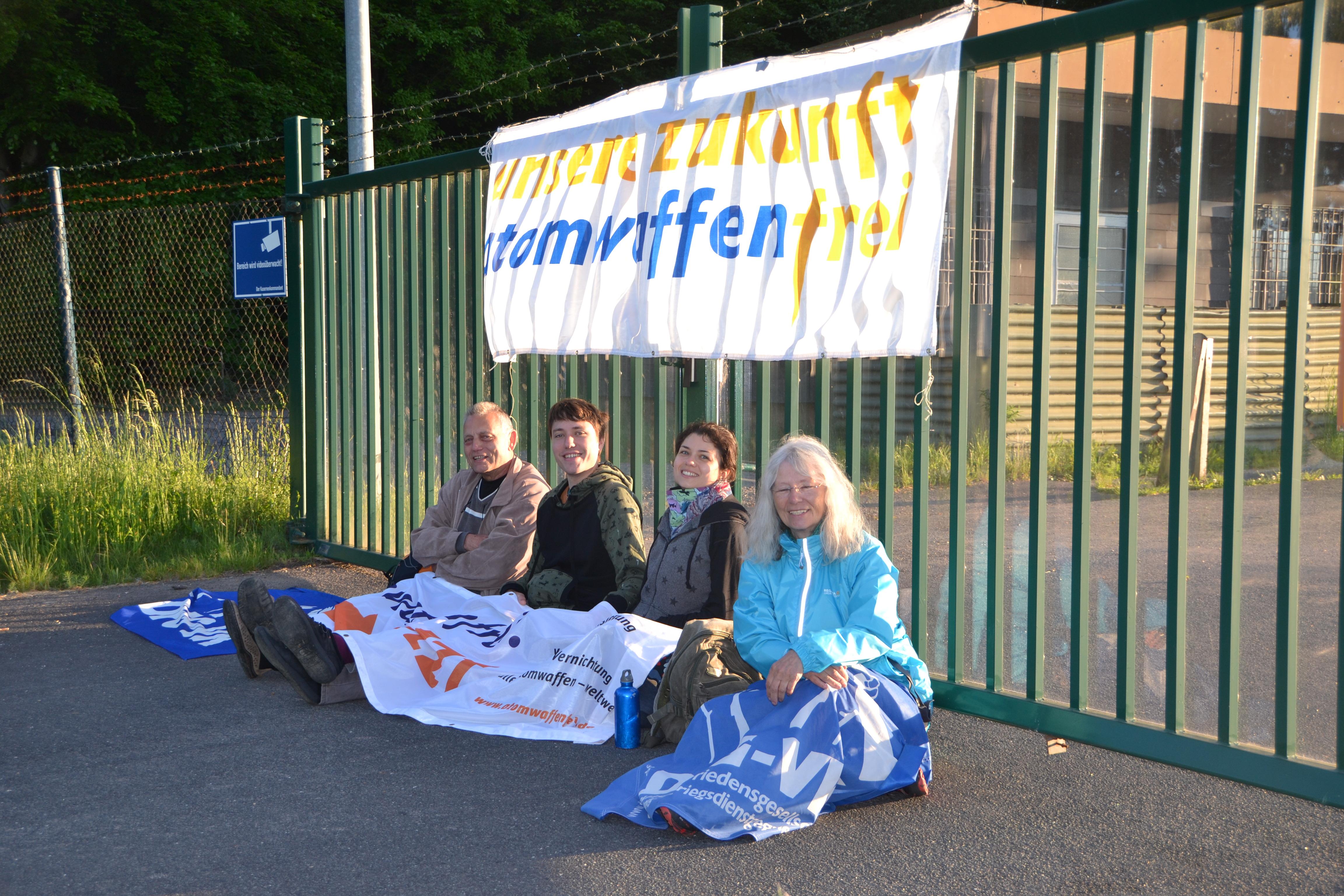 """Vier Aktivisten sitzen vor einem Tor, an dem ein Banner mit der Aufschrift """"Atomwaffenfrei"""" hängt. Sie haben sich weitere Banner über die Knie gelegt lachen in die Kamera. Von hinten scheint die aufgehende Sonne durchs Tor."""