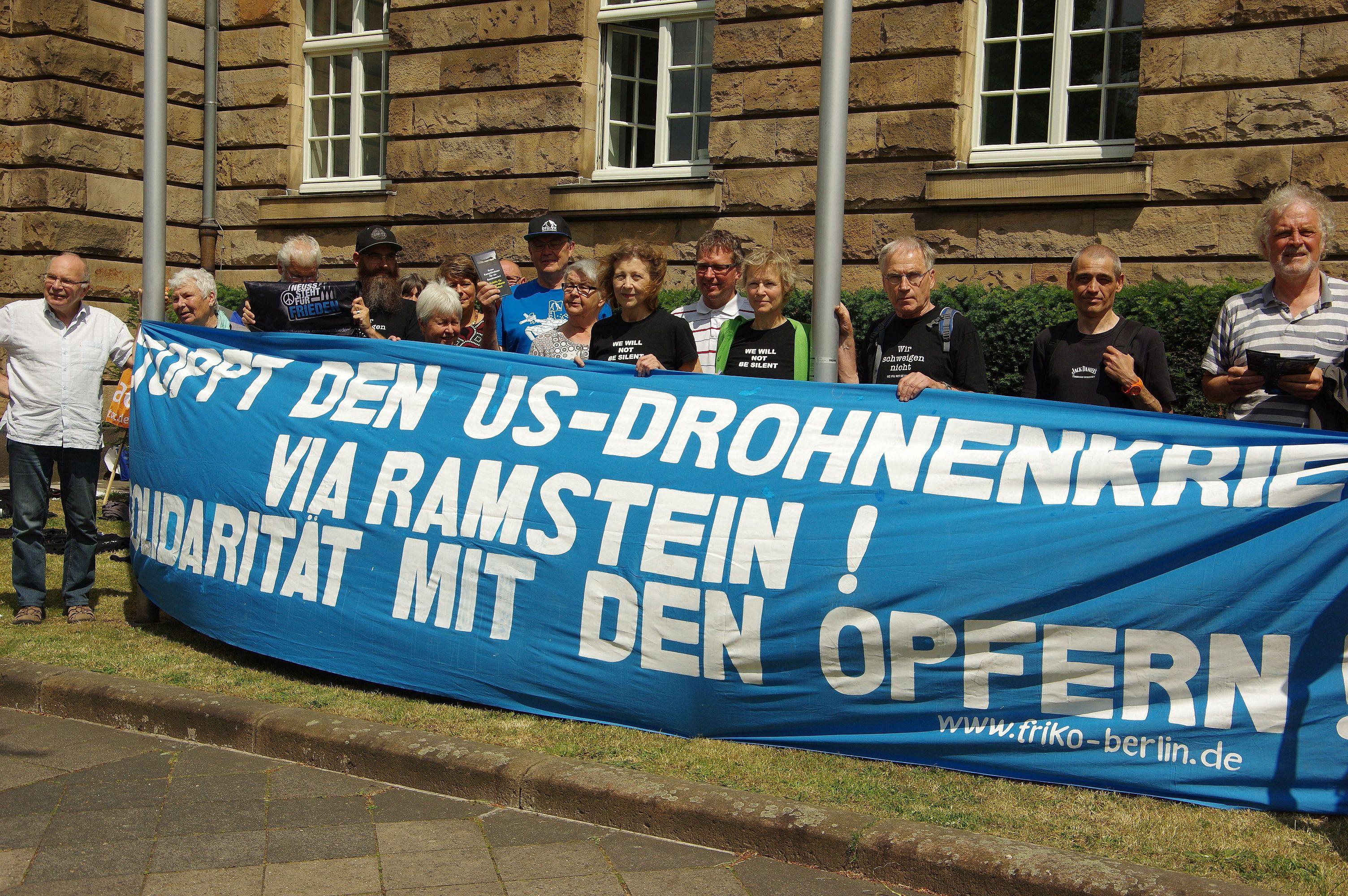 """Das Foto zeigt ein großes Transparent mit der Aufschrift """"Stoppt den US-Drohnenkrieg via Ramstein! Solidarität mit den Opfern!"""" Mehr als ein Dutzend Friedensaktivisten halten es hoch."""