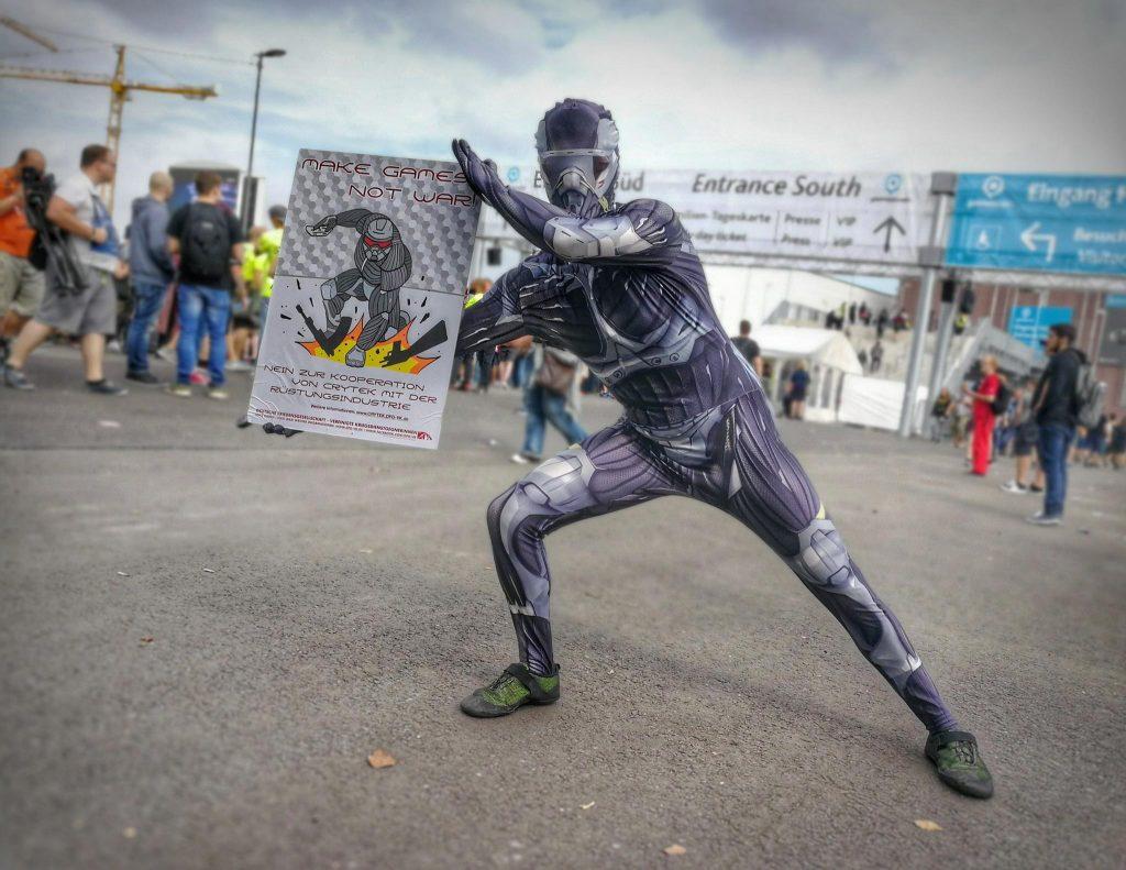 Zu sehen ist ein Mensch, der als Videospielfigur verkleidet ein Plakat hochhält. Darauf ist eine Videospielfigur zu sehen, die mit einem Fausthieb ein Ding zerstört, das sich erst beim näheren Hinsehen als Gewehr entpuppt.