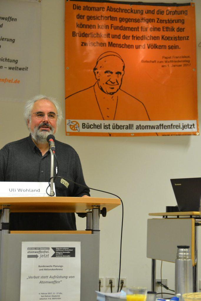 Uli Wohland ist ein Mann mit weißen Haaren und weißgrauem Vollbart, der in einem dunklen Hemd hinter einem Rednerpult steht und spricht. Im Hintergrund ist ein Werbeplakat der Kampagne Atomwaffenfrei jetzt! zu sehen, auf dem Papst Franziskus abgebildet ist.