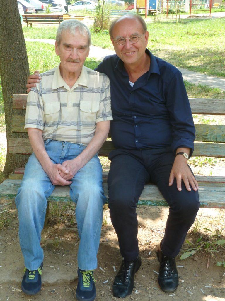 Zwei ältere Männer sitzen in der Sommersonne in einem Park. Der linke ist Stanislaw Petrow, ein schmächtiger Herr in hellem karierten Hemd, blauer Jeans und Turnschuhen. Er schaut ernst in die Kamera. Rechts sitzt Leo Ensel in dunklem Hemd und Hose. Er hat den Arm um Petrows Schulter gelegt und lächelt.