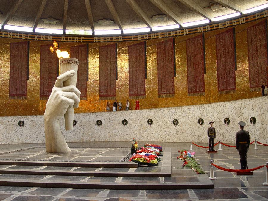Es ist das Innere einer runden Halle zu sehen, deren Wände in rot-goldenem feinen Mosaik gestaltet sind und in die zahlreiche Fahnen eingearbeitet sind, auf denen Tausende Namen der in der Schlacht von Stalingrad gestorbenen Menschen stehen. Im Vordergrund fällt der Blick auf eine mehrere Meter hohe Hand aus hellem Stein, welche aus dem dunklen Steinboden, der ein Grabmal andeutet, emporragt und ein schmales hohes Gefäß mit der Ewigen Flamme trägt. Auf dem Boden liegen Grabkränze und frische Blumen. Zwei Soldaten halten Wache.