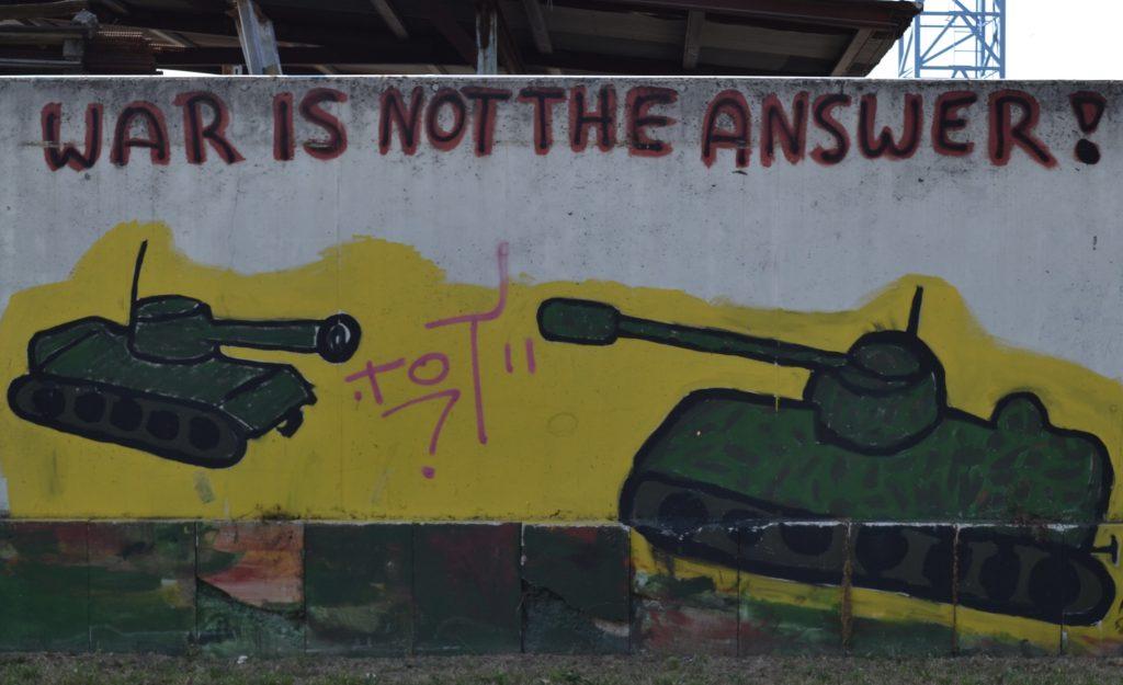 """Zwei auf eine Wand gemalte olivgrüne Panzer richten ihre Kanonen aufeinander. Darüber steht in roter Schrift: """"War is not the answer!"""""""