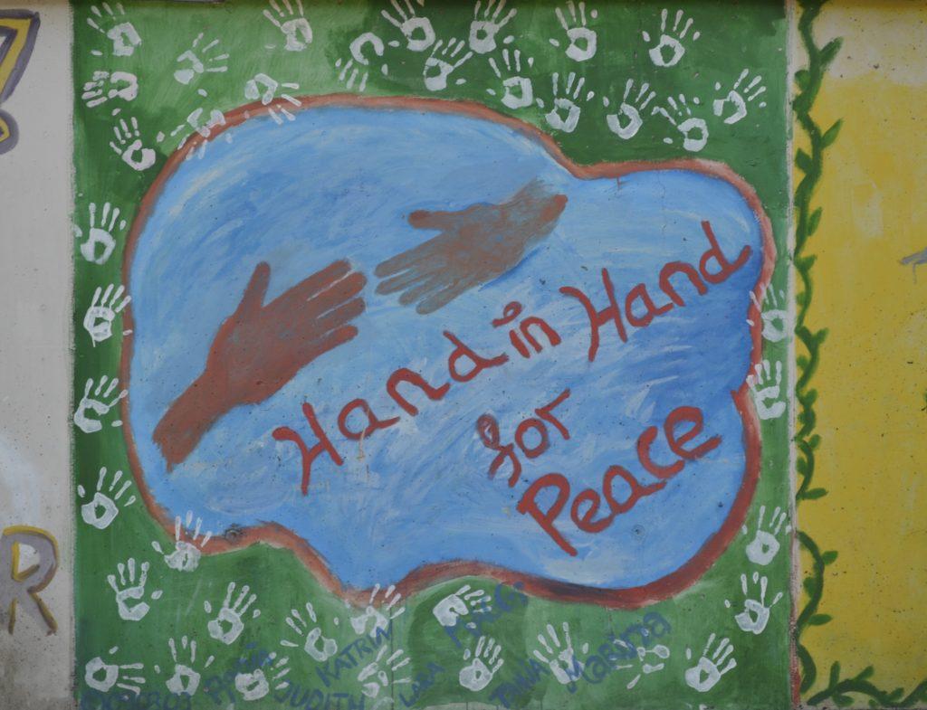 """Auf grünem Hintergrund, der mit weißen Handabdrücken bedeckt ist, sieht man in einer Art blauer Wolke zwei rötlich gefärbte Hände, die sich fast berühren, als wollten sich zwei Menschen gerade die Hand geben. Darunter steht """"Hand in Hand for Peace""""."""