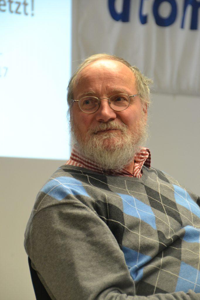 Ein älterer Herr mit Halbglatze und grauem Bart schaut freundlich am Fotographen vorbei offensichtlich zu einer anderen Person