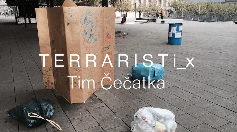Es ist ein Platz mit einem bekritzelten Karton und einigen kleinen, gefüllten Mülltüten zu sehen.