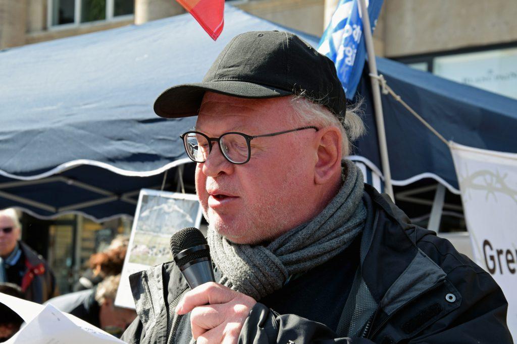 Ein älterer, etwas korpulenter Mann mit dunkler Baseballkappe und Brille spricht ins Mikro. Die Sonne scheint, im Hintergrund sind Transparente und Flaggen, darunter die blauweiße DFG-VK-Flagge, zu erkennen.