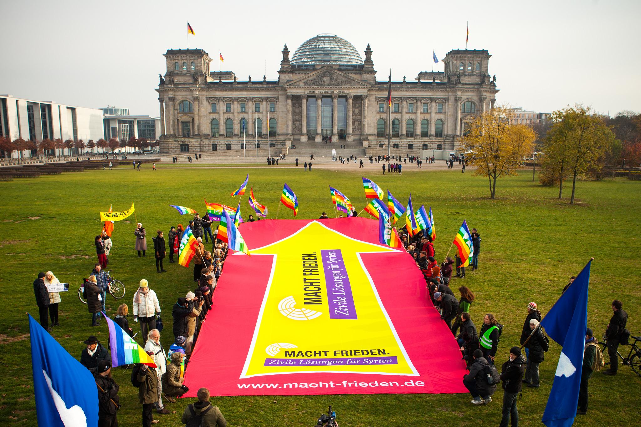 """Zu sehen ist ein riesiges Banner, das von zahlreichen Leuten mit Friedensflaggen gehalten wird und einen gelben Pfeil auf pinkem Grund zeigt, aus der Vogelperspektive. Im Hintergrund das Reichstagsgebäude. Der Pfeil ist auf das Gebäude gerichtet. Darauf steht: """"Macht Frieden. Zivile Lösungen für Syrien""""."""
