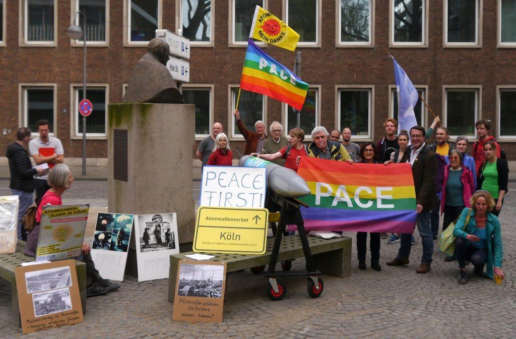 Rund um das steinerne Denkmal von Kardinal Frings sind eine Reihe von Friedensaktivisten mit Plakaten und Friedensfahnen zu sehen. Dazwischen ragt eine graue Atombombe - ein Modell der B61-12 - aus der Gruppe.