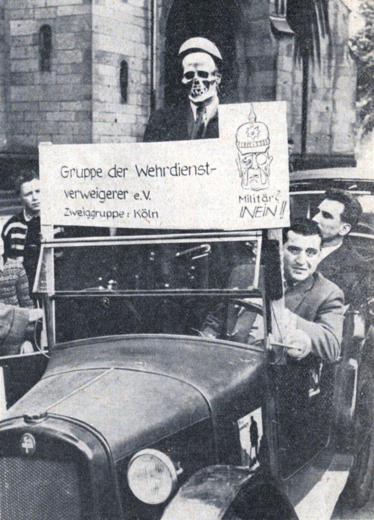 """Zwei junge Männer in dunklen Anzügen sitzen in einem alten Cabrio, über dessen Windschutzscheibe ein Plakat befestigt ist mit der Aufschrift: """"Gruppe der Wehrdienstverweigerer e. V. Zweiggruppe Köln."""" Unter einem skizzierten Bismarck-Kopf steht """"Militär? NEIN!"""" Hinter dem Plakat steht ein weiterer Mann im Wagen, der eine Totenschädelmaske trägt."""