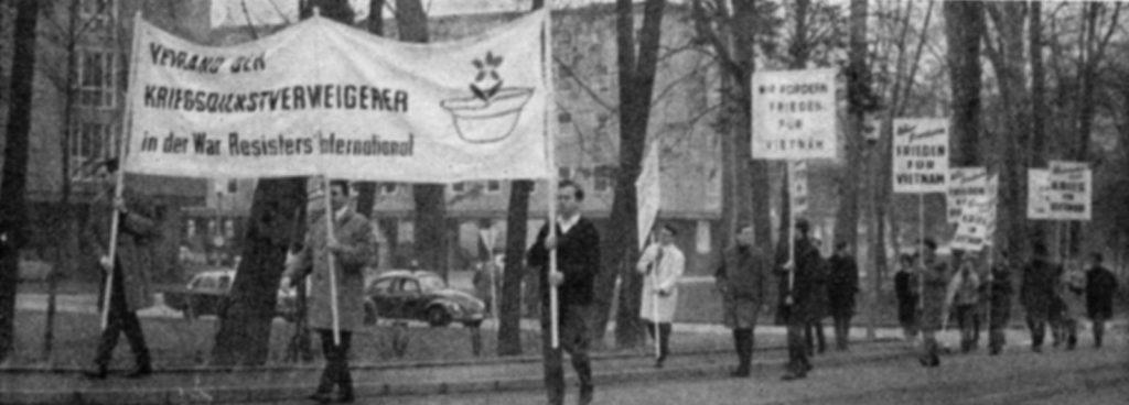 """Ein lockerer Demonstrationszug von jungen Männern mit Transparenten mit den Aufschriften """"Wir fordern Frieden für Vietnam!"""" und """"Verband der Kriegsdienstgegner in der War Resisters International"""""""