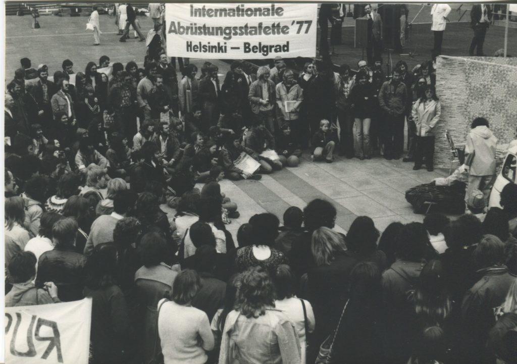 """Viele meist junge Menschen sitzen und stehen dicht gedrängt im Halbkreis und scheinen eine Ansprache zu erwarten. Ein Transparent hat die Aufschrift """"Internationale Abrüstungsstaffette '77 Helsinki - Belgrad"""""""