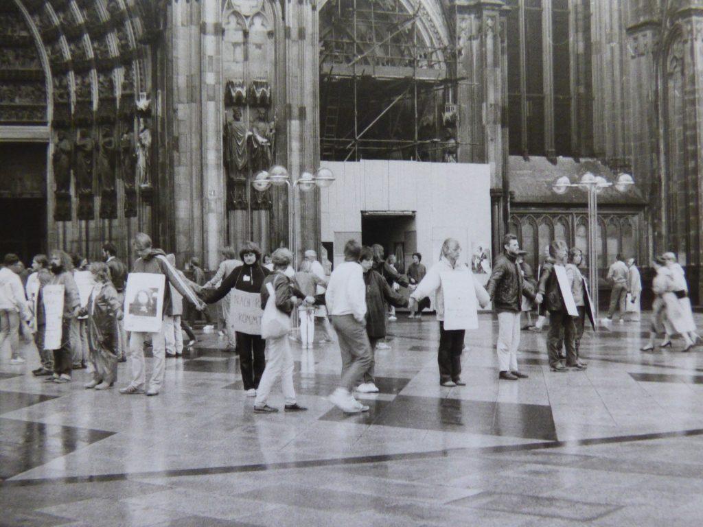 Vor dem Hauptportal des Kölner Doms stehen bei regnerischem Wetter Menschen mit den Rücken zueinander im Kreis und halten sich an den Händen. Sie haben sich Plakate umgehängt. Passanten bleiben stehen und sehen sich die Plakate an.