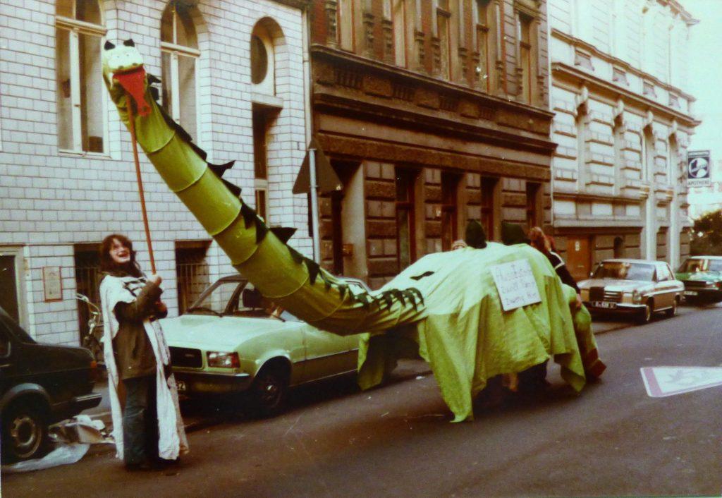 Ein aus hellgrünem Tuch bestehender Dinosaurier mit knallroter Zunge und dunkelgrünen Zacken auf Hals und Rücken steht in einer eng bebauten Straße - vielleicht in der Kölner Südstadt - und schaut in die Kamera. Eine Frau hält den Kopf mit einer Stange.