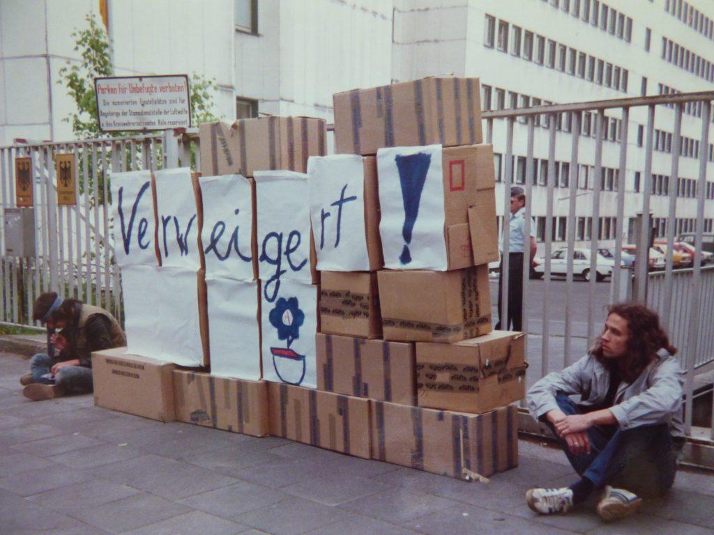 """Die Blockade besteht aus einigen gestapelten Pappkartons mit der Aufschrift """"Verweigert!"""". Rechts und links sitzt jeweils ein junger Mann."""