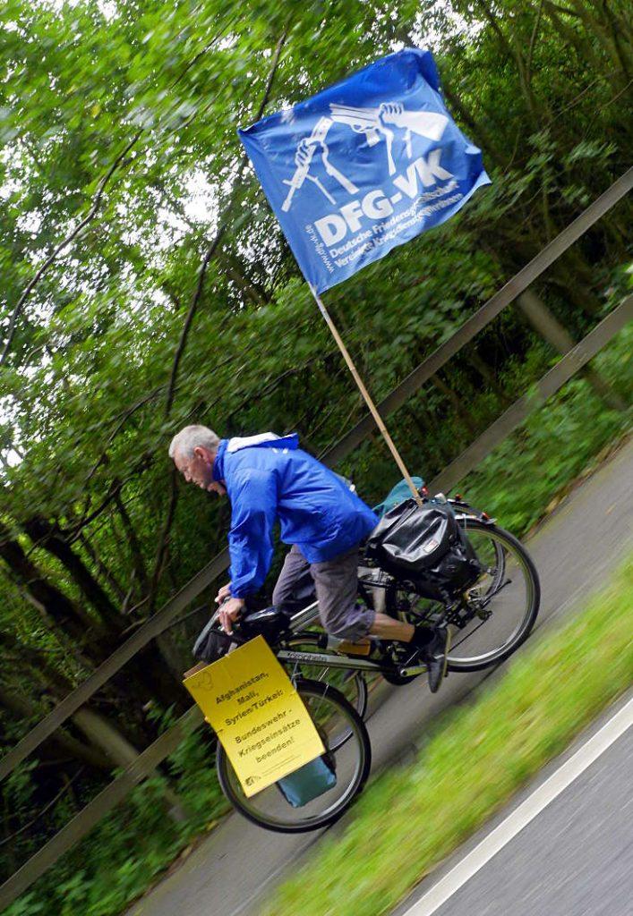 """Ein älterer Mann in blauer Windjacke saust auf dem Fahrrad an einer Hecke entlang. Das Fahrrad ist mit der blauweißen DFG-VK-Fahne geschmückt. An der Vorderradgabel ist ein Plakat zu sehen: """"Afghanistan, Syrien, Mali, Türkei: Bundeswehr-Kriegseinsätze beenden!"""""""