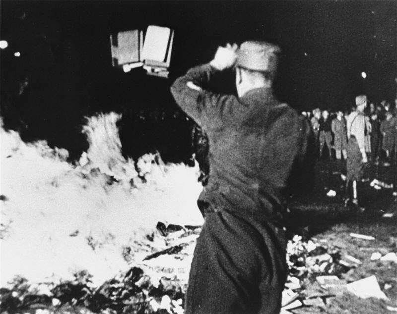 Eine Schwarz-Weiß-Aufnahme zeigt einen uniformierten Mann von hinten. Er wirft gerade ein Buch in das vor ihm brennende Feuer.