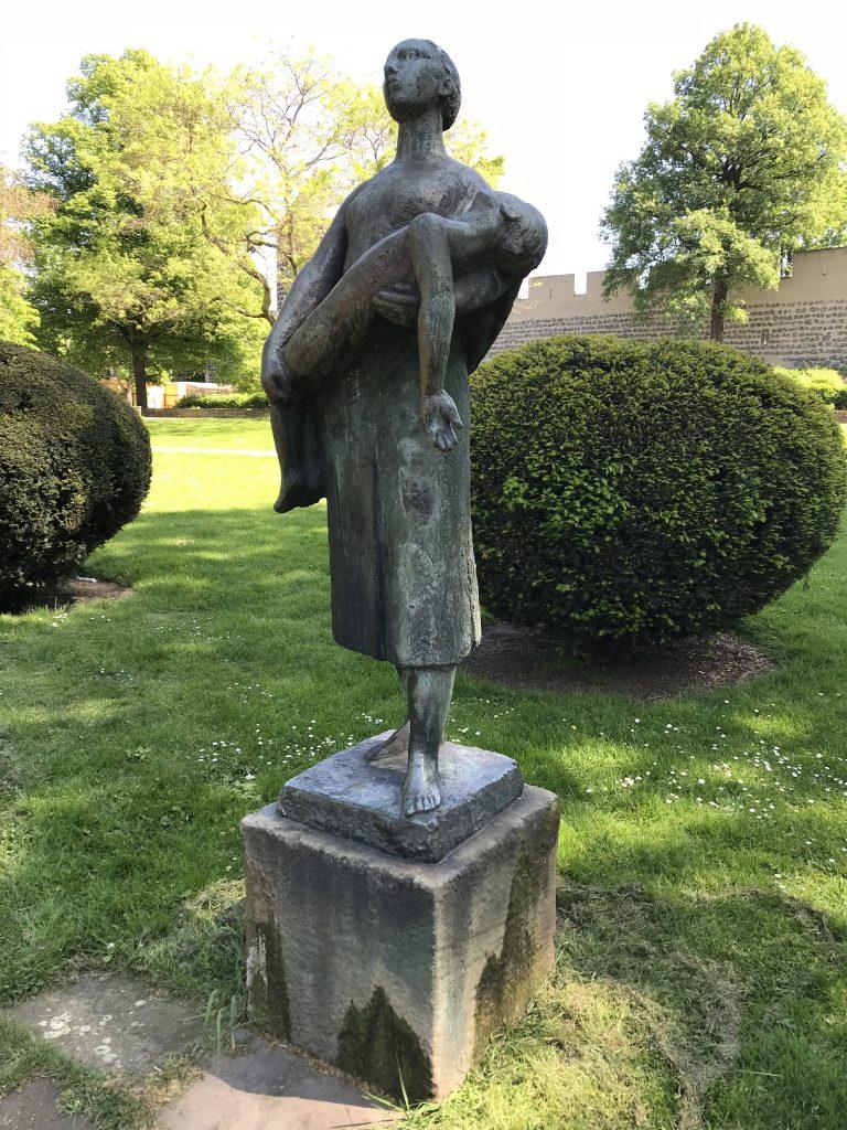 Bronzeskulptur einer Frau, die einen toten Jungen im Arm trägt. Im Hintergrund sind Parkbäume und ein Teil der Kölner Stadtmauer zusehen.