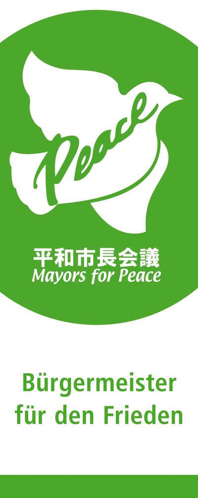 """Logo der Mayors for Peace in grün auf weißem Grund. Es zeigt eine weiße Taube mit dem Schriftzug """"Peace"""". Darunter sind japanische Schriftzeichen zu sehen und in der Zeile darunter """"Mayors for Peace"""". Ganz unten steht es auf deutsch: """"Bürgermeister für den Frieden""""."""