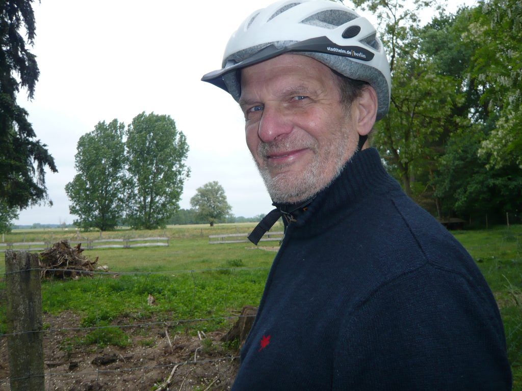 Ein älterer Herr mit kurzem hellgrauen Bart und blauen Augen, mit einem hellen Fahrradhelm auf dem Kopf und in dunklem Pulli schaut freundlich in die Kamera. Im Hintergrund ist eine Landschaft mit Feldern und Bäumen.