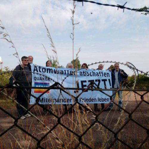 """Hinter einem Maschendraht- und Stacheldrahtzaun stehen sieben Menschen, die ein großes weißes Transparent vor sich tragen. Aufschrift: """"Atomwaffen abschaffen JETZT! Miteinander in Frieden leben!"""""""