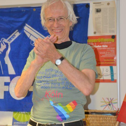 """Ein ältere schlanker Mann mit weißen Haaren und Brille strahlt glücklich den Betrachter an. Sein hellolivgrünes T-Shirt zeigt Friedensmotive: eine Friedenstaube in Regenbogenfarben und die Aufschrift """"Frieden"""" in vielen verschiedenen Sprachen, sowie """"Köln"""" als Schriftzug und Stadtsilouette."""