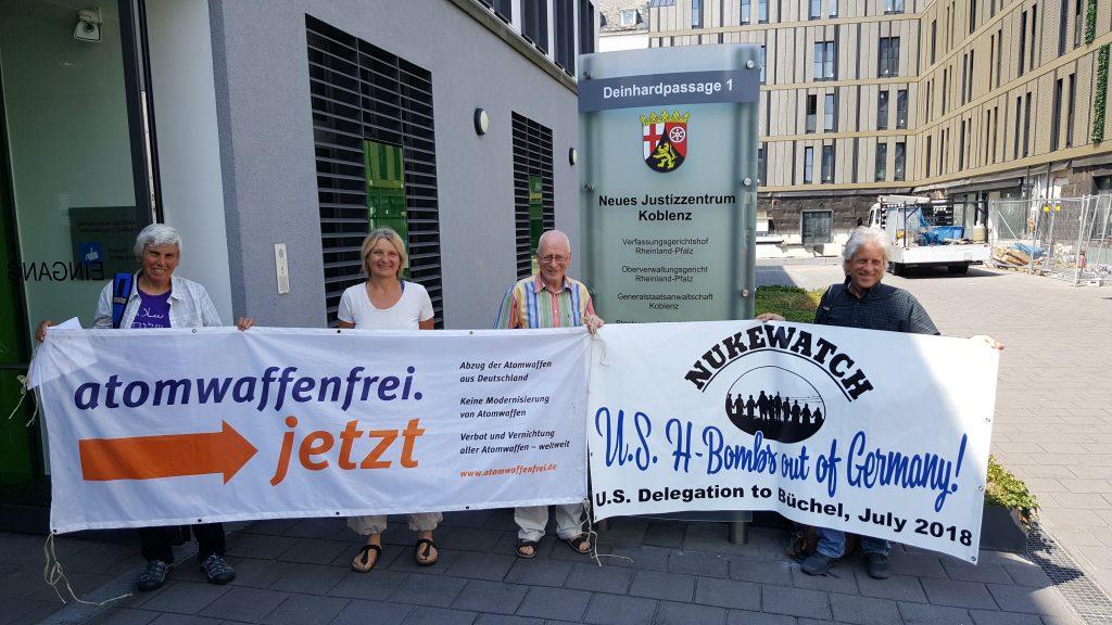 """2 Frauen und 2 Männer stehen lachend neben dem Eingang der Staatsanwaltschaft Koblenz. Sie tragen Transparente von """"Atomwaffenfrei jetzt!"""" und """"Nukewatch: US-Bombs out of Germany!"""" vor sich."""