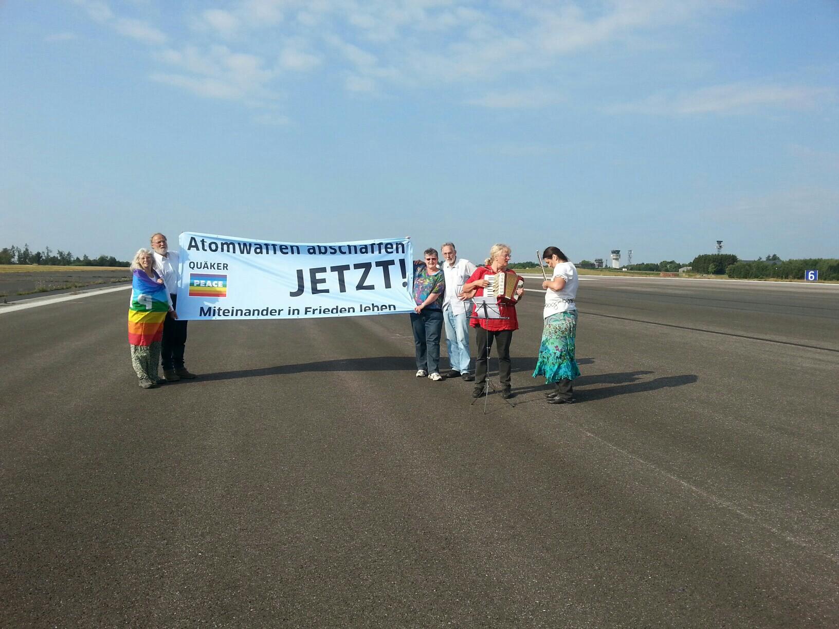 """Sechs bunt gekleidete Menschen stehen auf einer breiten asphaltierten Fläche - der Startbahn eines Flugplatzes - und tragen ein Transparent der Quäker zwischen sich: """"Atomwaffen abrüsten jetzt! Miteinander in Frieden leben""""."""