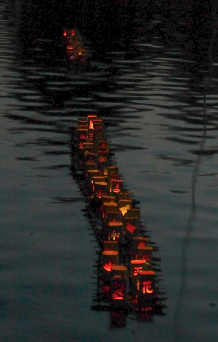 Eine Reihe von Papierlämpchen mit darin brennenden Teelichtern schwimmt auf einem dämmrigen Wasser.
