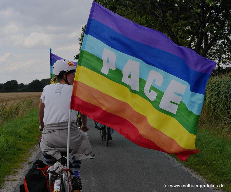 Eine Radfahrerin ist von hinten zu sehen. Eine große regenbogenfarbene PACE-Fahne, die am Hinterrad angebracht ist, wird vom Wind nach rechts getrieben, so dass man die Aufschrift gut sieht.