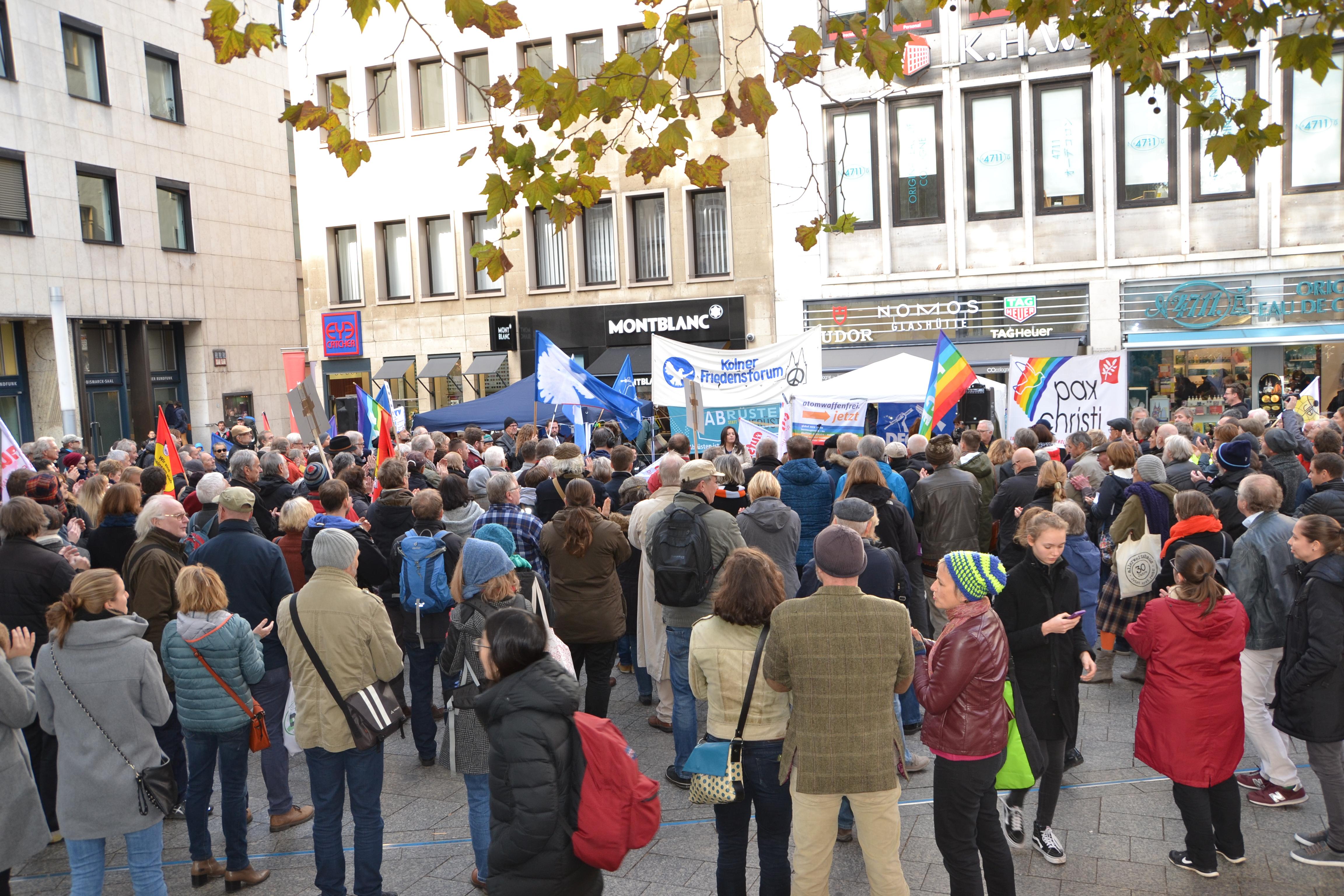 Eine ansehnliche Menge Zuhörer'innen; im Hintergrund Fahnen und das blauweiße Transparent des Kölner Friedensforum.