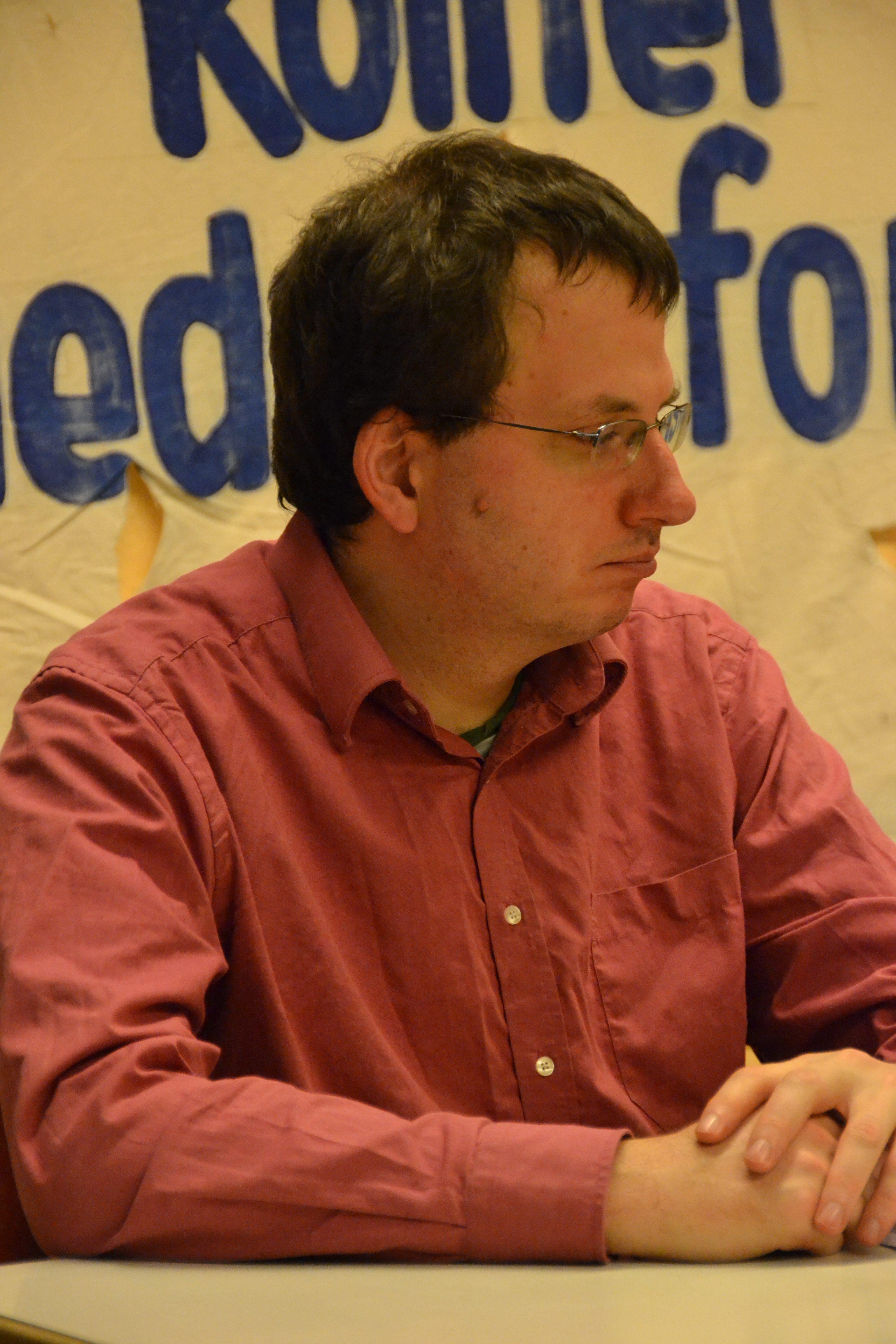 Ein junger nachdenklich schauender Mann mit dunklen Haaren und Brille in einem rötlichen Hemd am Tisch sitzend.
