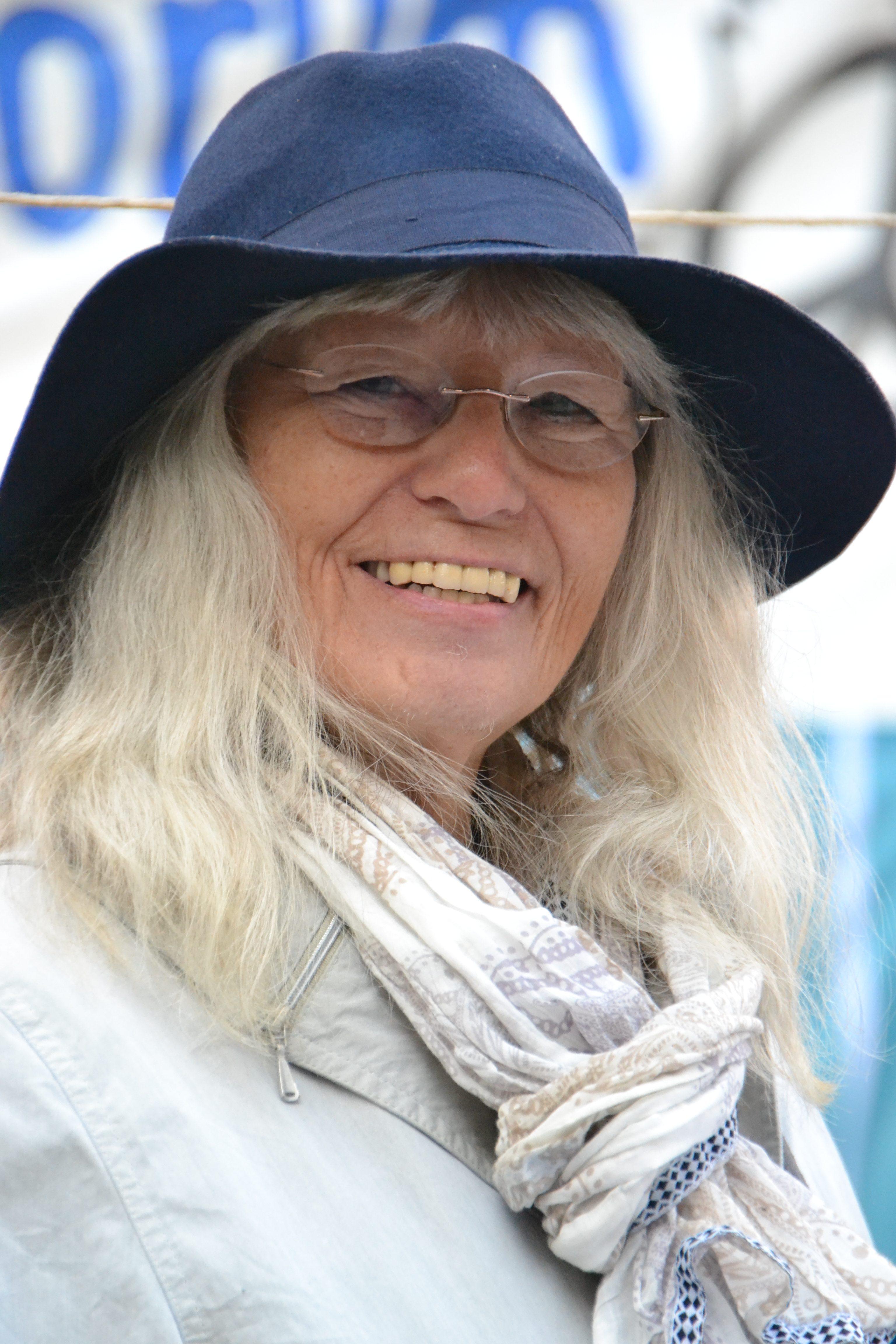 Kopfporträt einer fröhlich in die Kamera lächelnden hübschen Dame mit dicken welligen, über Schulter langen weißen Haaren, die unter einem dunkelblauen Hut mit breiter weicher Krempe hervorquellen.