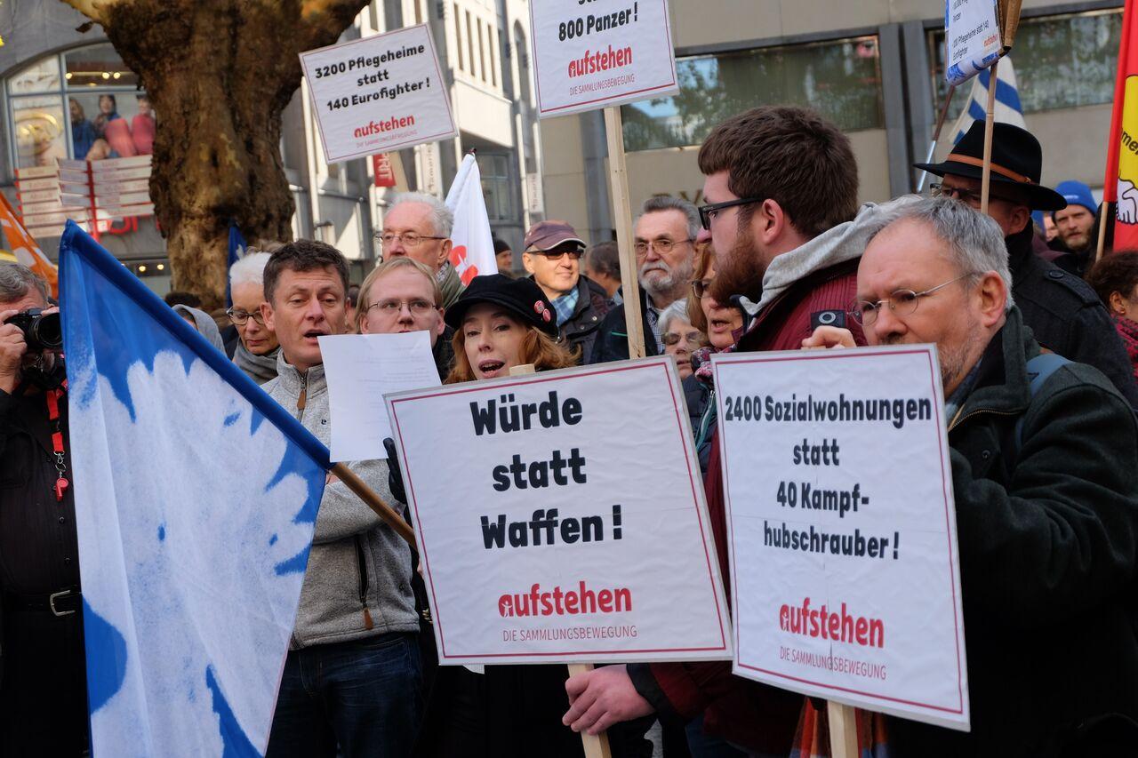 """Eine dicht gedrängte Gruppe Zuhörer*innen mit Schildern mit der Aufschrift """"Würde statt Waffen!"""""""