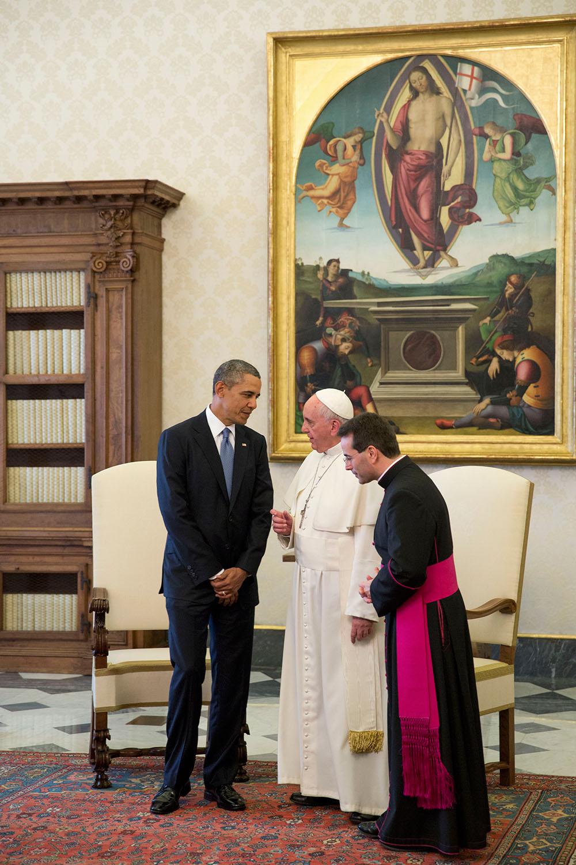 Obama steht links im dunklen Anzug neben Papst Franziskus in seinem weißen Gewand. Ein weiterer Geistlicher steht rechts. Im Hintergrund Sessel, ein schwerer Holzschrank und ein großes Gemälde der Auferstehung Jesu.