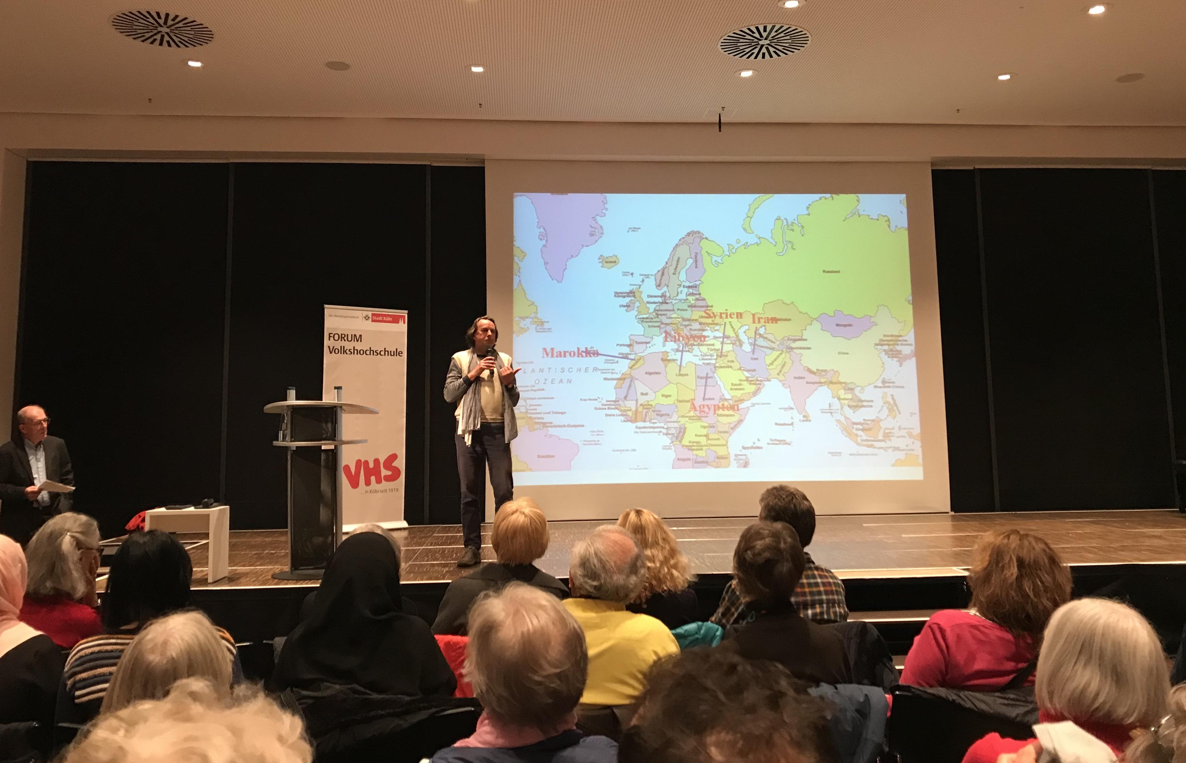 Roland steht auf der Bühne, im Hintergrund eine große Übersichtskarte über das östliche Mittelmeer und den Nahen und Mittleren Osten. Andreas Zumach steht links vor der Bühne. Im Vordergrund die sitzenden Zuschauerreihen.