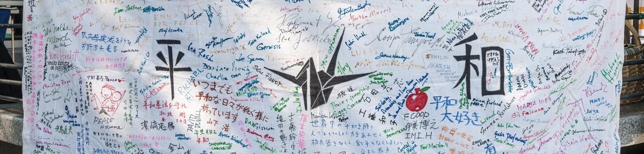 Ausschnitt eines mit vielen deutschen, japanischen und anderen Schriftzügen beschriebenes weißes Transparent. In der Mitte der gemalte Origami-Kranich.