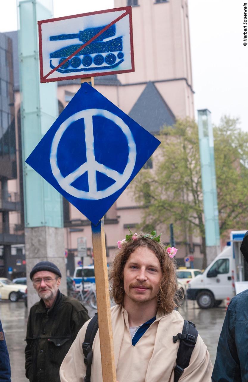 Ein junger Mann mit Blumenkranz im Haar hält ein Schild mit dem Friedenszeichen und einem durchgestrichenen Panzer in die Höhe.