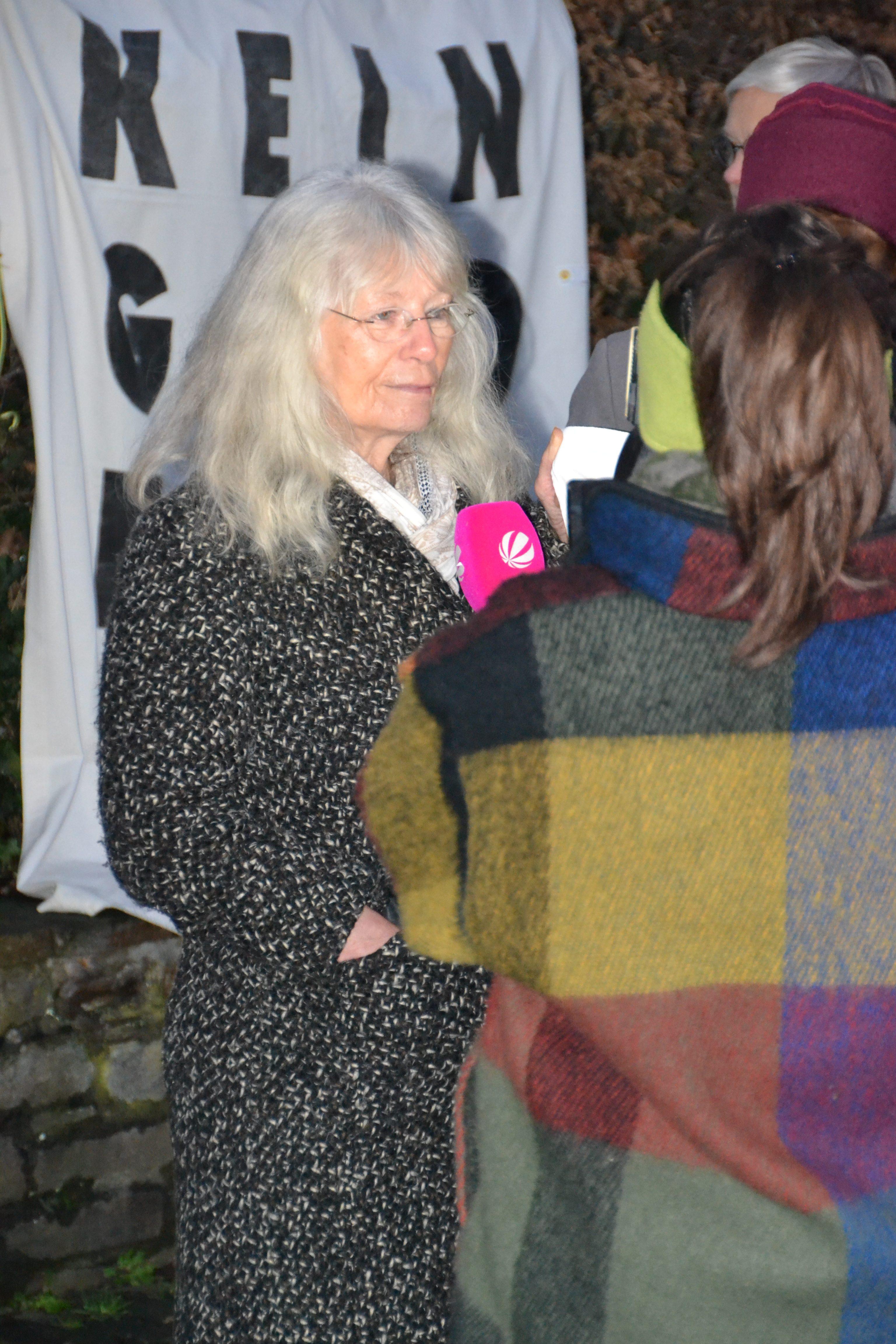 Eine hübsche ältere Dame in dunklem Wintermantel mit dicken, langen silbergrauen Haaren wird interviewt. Foto: Stefanie Intveen