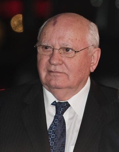 Porträt von Gorbatschow in dunklem Anzug. Sein Haarkranz ist weiß. Er schaut freundlich-skeptisch nach links.
