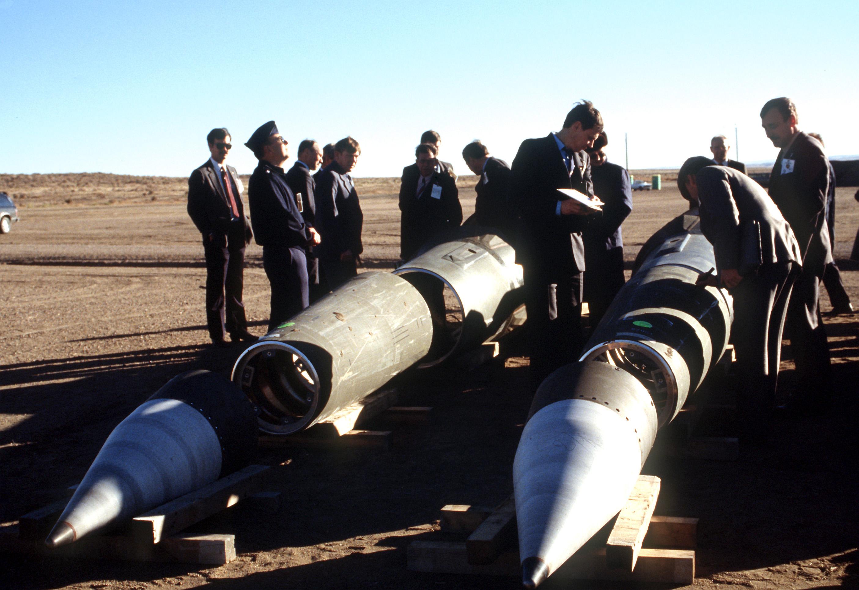 Im Gegenlicht sind zwei teilweise zerlegte Raketen zu sehen, die auf einer weiten verdorrten Ebene liegen. Dazwischen stehen Männer mit Soldatenkappen und Schreibzeug.