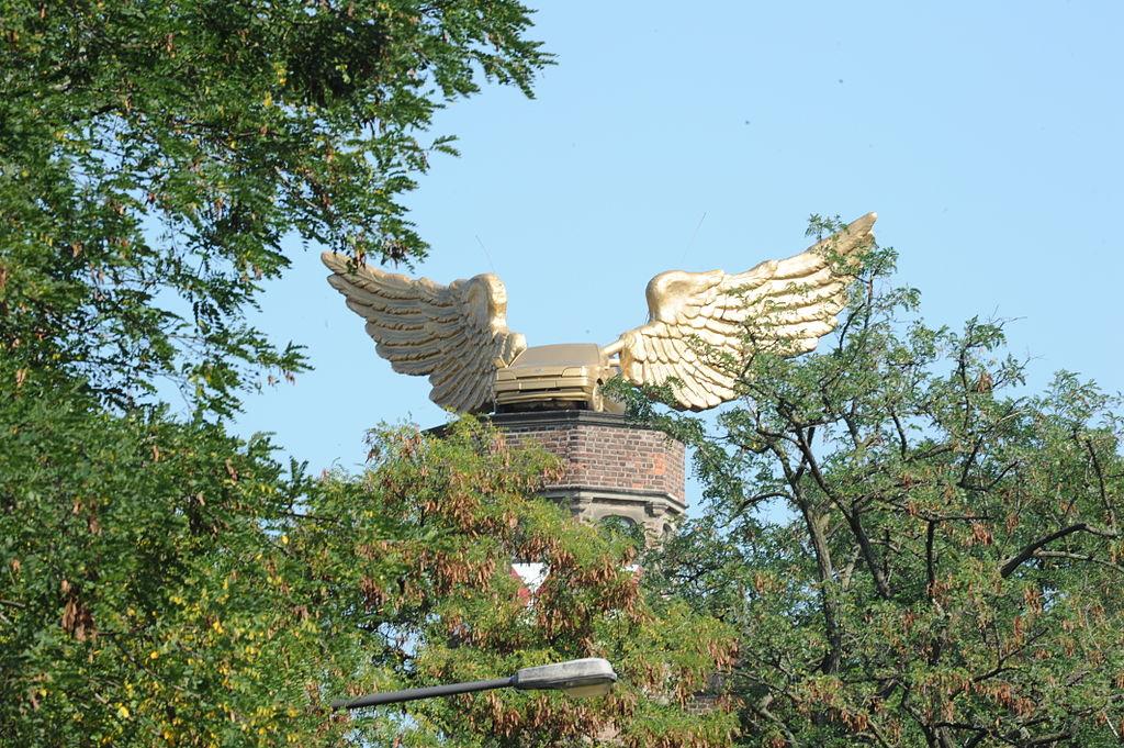 Zwischen Bäumen hindurch ist das goldene geflügelte Auto auf einem Backsteinturm zu sehen.